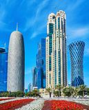 Futuristic architecture of Doha, Qatar. The flower beds in front  of the futuristic skyscrapers of West Bay neighborhood, the modern business center of Doha Royalty Free Stock Photos