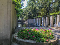 Flower beds and modern columned arcade in the Parc de Bercy, Paris, France. Flowerbed blooms in front of an arcade of columns in the summertime Parc de Bercy Stock Photos