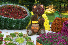 Flower beds in a shape of bear eating honey among different fruits with colorful chrysanthemums. Parkland in Kiev, Ukraine. Stock Photo