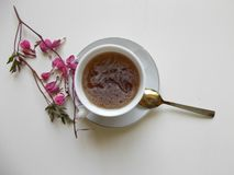 Tea in a white Cup, with pink flowers. Flower the bleeding heart next to the tea stock image