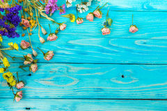 Flower border. Flower frame. Blue wood background Rustic. Top view. Lovely small roses and immortelles. Postcard invitation border. Copy Space you can place your Royalty Free Stock Image