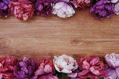 Flower border frame on wooden background Stock Photo
