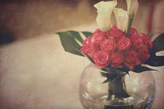 Flower bouquet. A beautiful flower bouquet with red roses in a vase on vintage sepia background Stock Photos