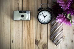 Flower bouquet and alarm clock and Necktie on wood background. Royalty Free Stock Images