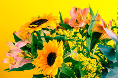 Flower bouquet with autumn flowers, lilies and sunflowers. Bright yellow background. Stock Photos