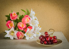 Flower  bouquet and a bunch of grape Royalty Free Stock Photo
