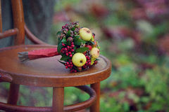 Flower bouquet on chair. Flower bouquet with apples on wooden chair outdoors with colorful nature background Stock Images