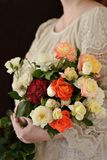Flower bouquet composition in an woman`s hands. White, orange and red roses bouquet in an woman`s hands stock photo
