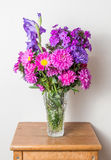 Flower bouquet in glass vase on wood Stock Image