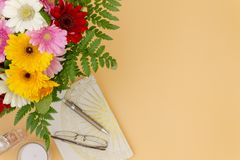 Flower bouquet with note pad pen glasses top view space for text royalty free stock image