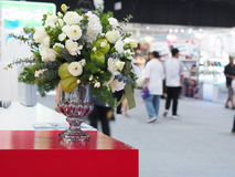 Flower bouquet on red table in shopping mall. Vase of flower bouquet on red table in shopping mall with crowd people background Royalty Free Stock Images