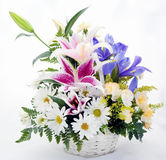 Flower Bouquet. Spring flower bouquet of daisies,lilies, and irises in white wicker basket Royalty Free Stock Images