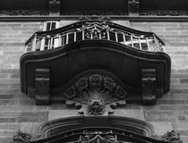 Flower bouquet under the balcony. Shot in black and white, detail on the sculpture on the facade of this historic building representing some characters. Set in Royalty Free Stock Photo