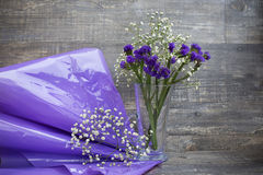 Flower bouquet in vase and purple packing paper. Purple and white flower bouquet in vase and purple packing paper on wooden background. Horizontal imagination Stock Photos