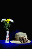 Flower bouquet in vase with straw hat still life Stock Photos