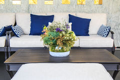 Flower bouquet in vase on table in living room. Beautiful bouquets in a glass vase on the table and sofa in the living room stock photography