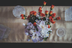 Flower Bouquet in Vase on Table Surrounded With Ashtrays and Decanters Stock Image