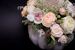 Flower bouquet in a white pumpkin on a black background, a mixture of flowers, peony rose, eucalyptus, chrysanthemum stock image