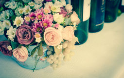 Flower bouquet and wine bottles Royalty Free Stock Photos