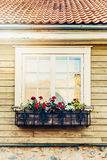 Flower box hanging in front of old house window. Flower box hanging in front of old wooden house window Stock Photos