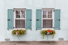 Double Window Pastel. Flower boxes adorn these symmetrical windows with open shutters in this vintage, Southern look Stock Image