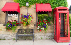 Flower boxes, Hanging Plants, Telephone booth. Beautiful flower boxes and hanging plants on a yellow brick wall along a sidewalk with a telephone booth Stock Images