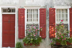 Flower boxes red shutters. House with red shutters and decorative flower boxes at the windows Royalty Free Stock Photos