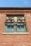 Flower boxes in a window with a brick wall Royalty Free Stock Images