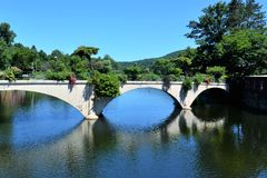 Flower Bridge across Deerfield River in Shelburne Falls. MA. Bridge is reflected in the blue river water. Flowers stream over the sides of the bridge and grow Royalty Free Stock Photos