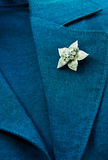 Flower brooch. On a business female suit of blue color Stock Photos