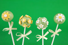 Flower cake pops. Round-shaped mini cakes covered with chocolate and decorated with fondant flowers Royalty Free Stock Photography