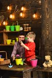 Flower care watering. Soil fertilizers. happy gardeners with spring flowers. bearded man and little boy child love. Flower care watering. Soil fertilizers. happy stock images