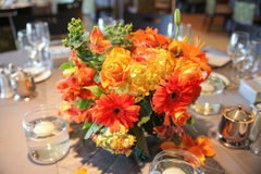 Flower centerpiece. An orange and yellow flower centerpiece of roses, gerbera daisies and carnations on a party table Royalty Free Stock Photography