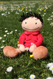 Flower child. Happy doll cherishing a flower during a sunny day in summertime Royalty Free Stock Photos