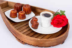 Flower, coffee and cakes. Cake canneles from France on wooden tray with coffee with flower royalty free stock photos