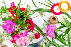 Flower composition with a bouquet of pink peony flowers, cornflowers and red roses and colored ribbons on a white background, top. View flat lay royalty free stock photo