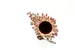 Flower composition. Cup of tea and spoon with dried rose flowers. Square, top view, flat lay royalty free stock images