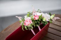 Flower composition, wedding bracelet of pink rose with ribbon and groom boutonniere on wooden table. Flower composition, wedding bouquet of pink rose with ribbon stock images
