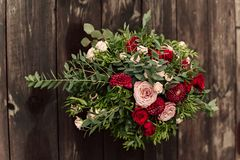 Flower composition on wooden wall. Flower composition in wooden wall on the served table in the restaurant. Wedding dinner Royalty Free Stock Photography