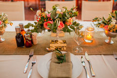 Flower compositions on the wedding table in rustic style. Wedding decorations with their own hands. Royalty Free Stock Image