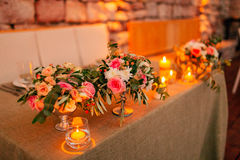 Flower compositions on the wedding table in rustic style. Wedding decorations with their own hands. Royalty Free Stock Photo