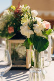 Flower compositions on the wedding table in rustic style. Wedding decorations with their own hands. Royalty Free Stock Images