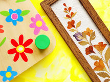 Flower crafts hobby. A handicraft image of a wooden press for drying and pressing flowers, and a sample of colorful dried pressed flowers and leaves in a wood Royalty Free Stock Image
