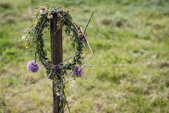 Flower crown hanging on a stick. Flower crown left hanging on a stick in the garden Stock Photo
