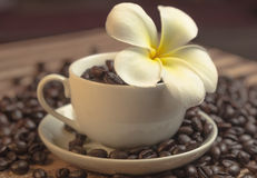 Flower in a cup of coffee. White cup and saucer and a flower royalty free stock photo