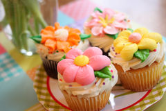Flower cupcakes. Four bright cupcakes with sugared frosting flower decorations sit on a green plaid plate Stock Image