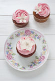 Flower cupcakes. Pink flower cupcakes with white flowers on floral plate Royalty Free Stock Photo