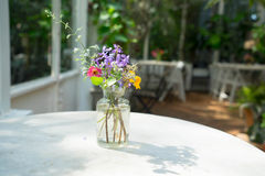 Flower decorate on the table. Flower in the glass vase on the wood table in the garden Stock Images