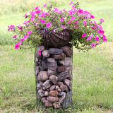 Flower decoration. Basket full of petunias standing on the decorative pile of stones Royalty Free Stock Photo