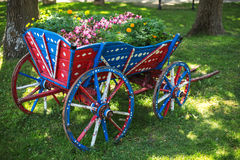 Flower decoration in the garden and wooden wagon Stock Photo